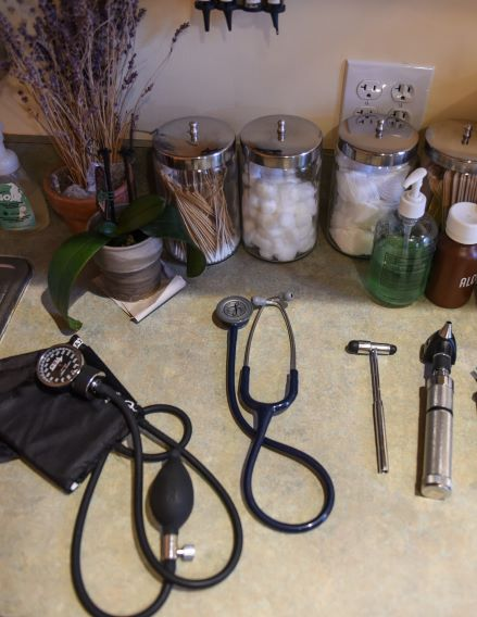 Table with medical tools like stethoscope, rubber hammer, cotton balls