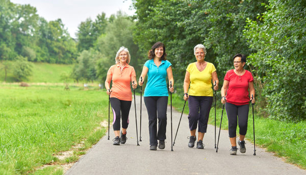 four older women walking for exercise on a path through a park