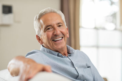 Older healthy man sitting on a couch smiling