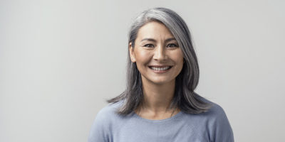 Beautiful asian with grey hair smiling standing near the wall